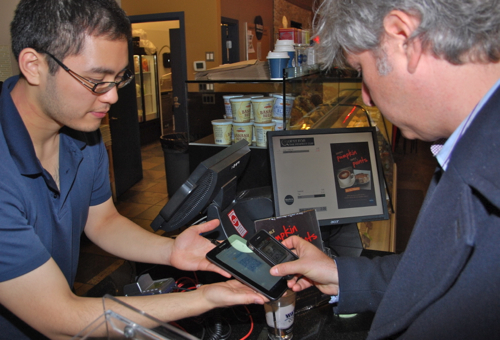 A customer buys a coffee with bitcoin at a coffee shop in Vancouver, Canada, where the world's first bitcoin ATM was installed in March, 2014. © Deborah Jones 2014