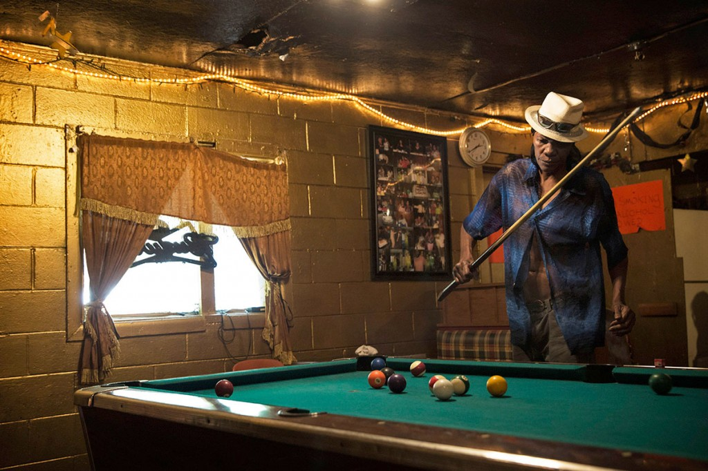 Melvin Williams, 64, plays pool in Odessa's Place, a small one-room bar in the impoverished Baptist Town neighborhood of Greenwood. Odessa Nicks, 85, opened the bar in 1963 and has kept it going in old age so that she remains occupied. Williams pays $200 a month in rent to live in an apartment directly behind the bar. Photo by Edmund D. Fountain, special to ProPublica. © 2014