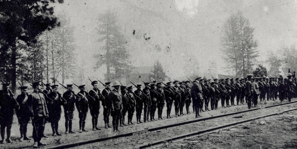 "The Nicola Valley Museum caption for this photo is ""Soldiers lined up on track, Merritt. 1st contingent BC Horse — leaving for Valcartier Que."" The date is probably Aug. 15 1914, the first of three days of departures from the valley by members of the militia regiment and volunteers. ""Pathetic Scenes at Local Depot,"" reads the Aug. 21 Merritt Herald headline atop the weekly newspaper's story on the departures."