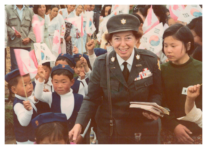 A photograph of Dr. Lotta in Korea around 1970 catches the essential humanitarian, in uniform and her notebook in hand and children at hand. Photo courtesy of Unitarian Service Committee