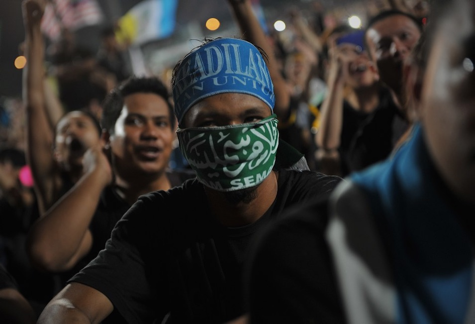 "The original Wikipedia Commons caption reads (more or less): ""Thousands of Malaysians dressed in mourning black gathered in Kuala Lumpur on May 8, 2013 to denounce national elections that they claim were stolen through fraud by the coalition that has ruled for 56 years."" Firdaus Latif is the photographer."
