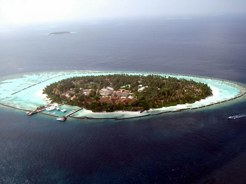 "Climatically and politically, the Maldives is pretty much a hell on Earth, writes Jonathan Manthorpe, with the green, ""eco-friendly"" resorts are owned by five families, who are also at the heart of a small coterie of inter-related clans that control everything that moves on the islands.  The islands and atolls of the Maldives are, on average, only one-and-a-half meters above current sea level, writes Jonathan Manthorpe, making the Maldives the Earth's lowest-lying country. Above, Kurumba Island in the Maldives. Photo by PalawanOz via Wikipedia"