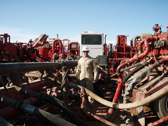 Halliburton contracts with energy giants to find and exploit oil and gas fields, sells the expertise of its geologists and engineers, and  builds machinery to provide those services.Above, a fracking operation. Photo by Joshua Doubek/Wikipedia