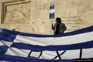 A protester holds a banner in Greek colors in front of the parliament building during an anti-austerity rally in Athens, Greece, June 29, 2015. REUTERS/Yannis Behrakis