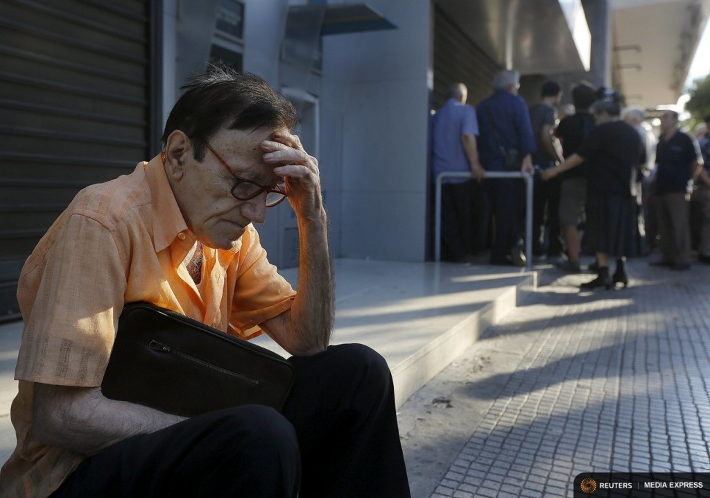 Giorgos, a 77-year-old pensioner from Athens, sits outside a branch of the National Bank of Greece as he waits along with dozens of other pensioners, hoping to get their pensions in Athens, Greece June 29, 2015. REUTERS/Yannis Behrakis