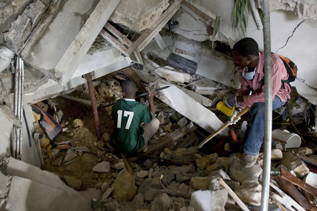 Two Haitians use crowbars, shovels and their hands to clear rubble in an attempt to reach survivors at the Montana hotel that collapsed after an earthquake measuring 7 plus on the Richter scale rocked Port au Prince, Haiti, on January 12, 2010. Photo by United Nations Development Programme.