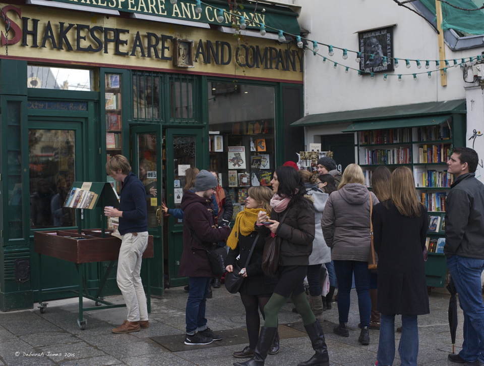 Shakespeare and Company is near the top of globally popular book stores. Above, the cramped Paris bookshop has an overflow of customers, rain or shine, awaiting their their turn inside.  Photo by Deborah Jones 2015