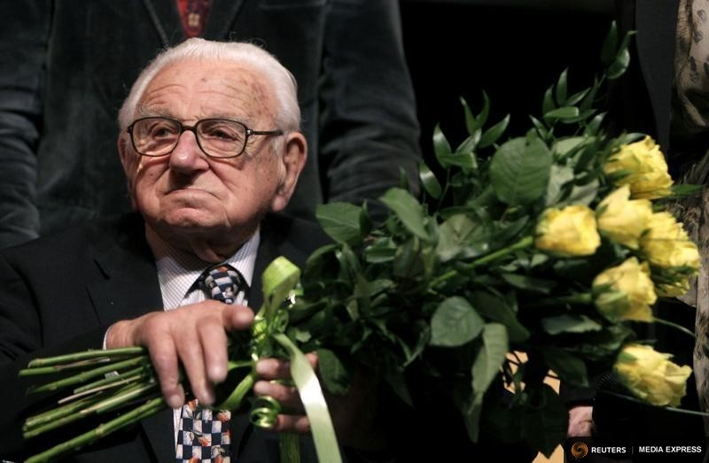 "Nicholas Winton, aged 101, holds flowers while sitting on a stage after the premiere of the movie ""Nicky's family"" which is based on his life story in Prague January 20, 2011.     REUTERS/Petr Josek"