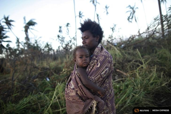 A woman carrying her baby walks past fallen trees in Tanna March 18, 2015. International aid agencies ramped up appeals for cyclone-hit Vanuatu, warning that the powerful storm which affected more than two-thirds of the South Pacific island nation had wiped out crops and destroyed fishing fleets, raising the risk of hunger and disease.  Residents of the southern island of Tanna said food and basic supplies were running low while relief workers were still battling to reach many islands pummelled by Cyclone Pam's gusts of more than 300 kph (185 mph) on Friday and Saturday.  REUTERS/Edgar Su