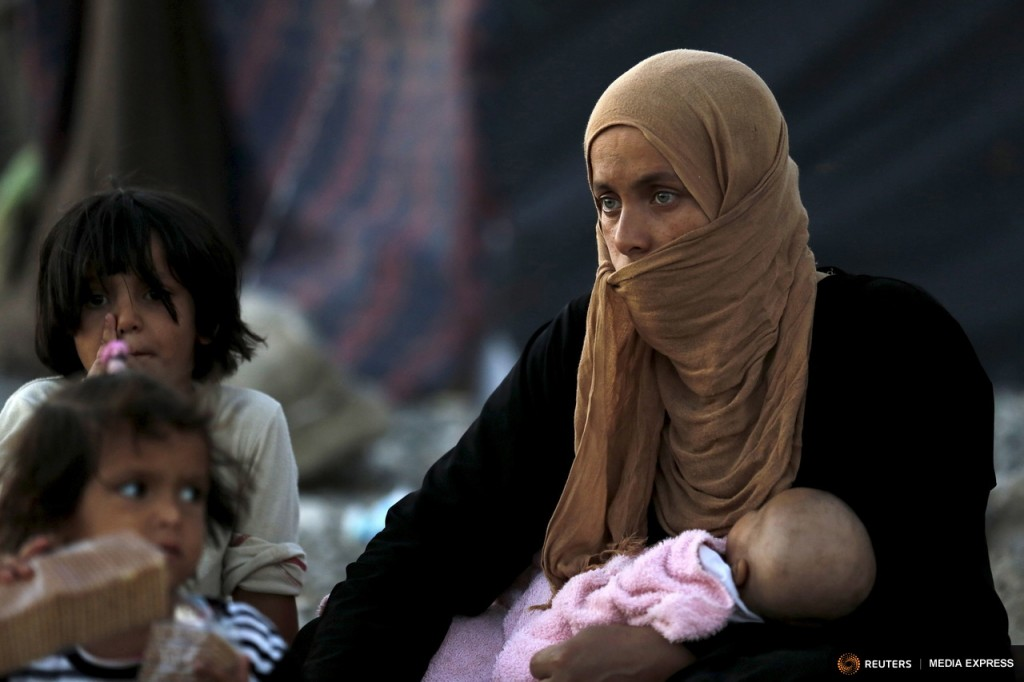 A refugee from the northern Syrian town of Tel Abyad and her children wait while spending the day in Akcakale, in Sanliurfa province, Turkey, in this June 18, 2015 file picture.  REUTERS/Umit Bektas/Files
