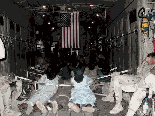 Bound, hooded captives, being flown to Guantanamo. United States Department of Defence photo