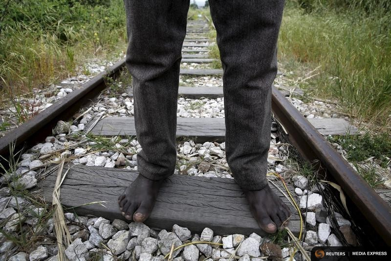 26-year-old Azam from South Sudan stands on rail tracks after failing to flee to Italy in the western Greek town of Patras April 28, 2015. Afghan, Iranian and Sudanese immigrants, living precariously in abandoned factories in Patras, southwest Greece, try to stow away on nearby ferries to Italy as they seek a better life in Europe beyond crisis-hit Greece. Shocked after as many as 900 people drowned last month in the worst Mediterranean shipwreck in living memory, European Union leaders have agreed to triple funding for sea patrols, but disagreement persists on what to do with those fleeing conflict and poverty in the Middle East and Africa. Some in Patras are recent arrivals, often travelling via Turkey, others have languished in the empty buildings for as long as two years. REUTERS/Yannis Behrakis