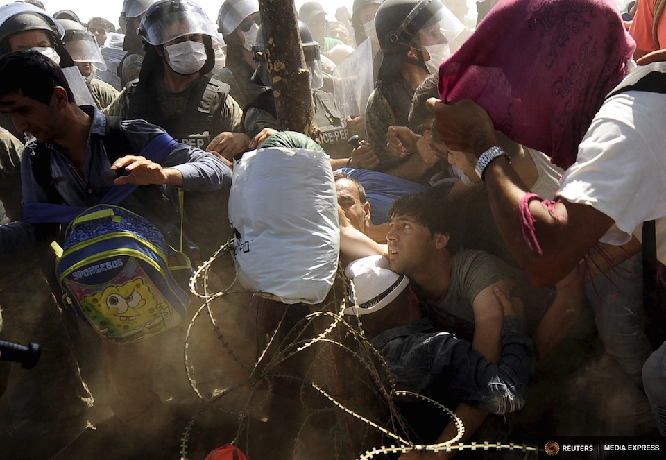 Migrants fall as they rush to cross into Macedonia after Macedonian police allowed a small group of people to pass through a passageway, as they try to regulate the flow of migrants at the Macedonian-Greek border September 2, 2015. REUTERS/Ognen Teofilovski