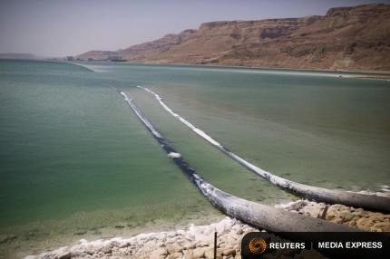 Pipes that pump water cross through evaporation pools, which today make up the southern part of the Dead Sea, Israel July 27, 2015. The Dead Sea is shrinking, and as its waters vanish at a rate of more than one meter a year, hundreds of sinkholes, some the size of a basketball court, some two storeys deep, are devouring land where the shoreline once stood.Picture taken July 27, 2015. REUTERS/Amir Cohen