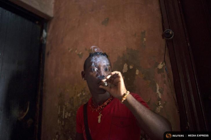 Santeria practitioner Yuris Landis, a 27-year-old nurse, smokes a cigar during a ceremony of the Afro-Cuban religion Santeria to attract spirits of dead ancestors to ask for guidance in downtown Havana, August 18, 2015. Santeria adherents can only hope the upcoming visit from Pope Francis will somehow nudge the Church toward recognizing the millions of Cubans who identify with both religious traditions. Picture taken on August 18, 2015. REUTERS/Alexandre Meneghini