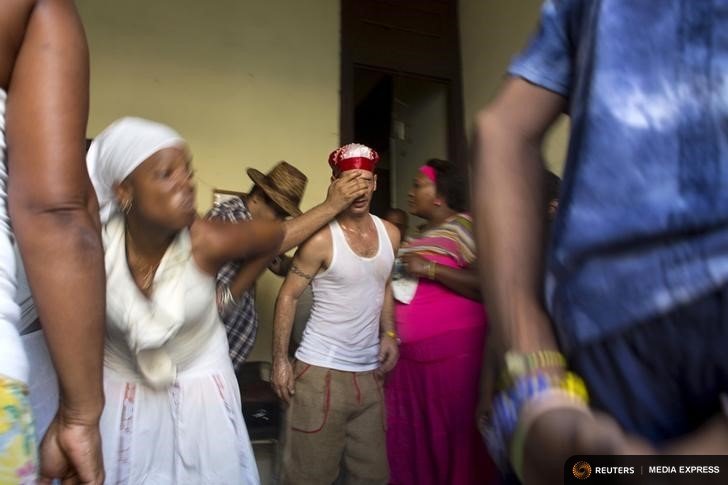 Santeria practitioner Lyan Hernandez, 36, (C) undergoes a brief fit of spirit-induced convulsions during a ceremony to attract spirits of dead ancestors to ask for guidance in downtown Havana, August 18, 2015. Santeria adherents can only hope the upcoming visit from Pope Francis will somehow nudge the Church toward recognizing the millions of Cubans who identify with both religious traditions. Picture taken on August 18, 2015. REUTERS/Alexandre Meneghini