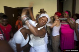 Santeria practitioners undergo a brief fit of spirit-induced convulsions during a ceremony to attract spirits of dead ancestors to ask for guidance in downtown Havana, August 18, 2015. Santeria adherents can only hope the upcoming visit from Pope Francis will somehow nudge the Church toward recognizing the millions of Cubans who identify with both religious traditions. Picture taken on August 18, 2015. REUTERS/Alexandre Meneghini