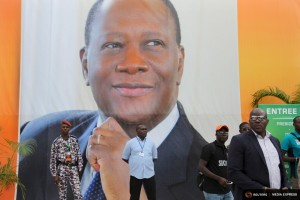 "Supporters of President Alassane Ouattara stand in front of a poster of Ouattara at a pre-election gathering for him in Abidjan, Ivory Coast, September 13, 2015. From Abidjan's packed airport arrivals hall to the buildings mushrooming across the capital, Ivory Coast is booming, a rare African bright spot as the world's biggest cocoa producer bounces back from a 2011 civil war. Buyers of luxury apartments include Ivorians living overseas, while promoters from Morocco, Turkey and China are attracted by tax breaks. Elections - the source of national unrest four years ago - are due in a month but there is no let-up in investment given expectations of an easy victory for incumbent Ouattara. The government predicts 9.6 percent growth this year, making the former French colony the standout performer on a continent hammered by a slump in commodity prices, capital outflows and tumbling currencies.    REUTERS/Joe PenneyPICTURE 8 OF 33 FOR WIDER IMAGE STORY ""IVORY COAST IS BOOMING"". SEARCH ""BOOMING PENNEY"" FOR ALL IMAGES"