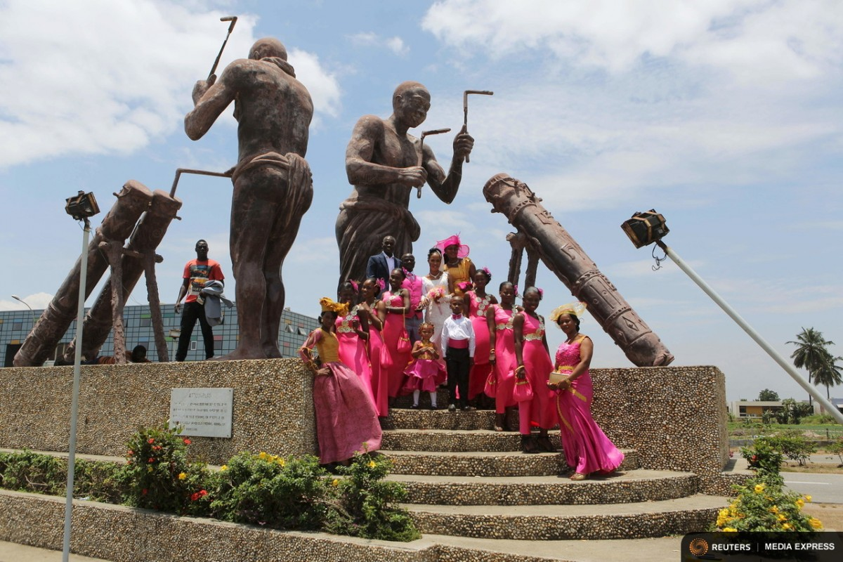 "A bride and groom pose for a wedding picture under a statue near the Radisson hotel construction site in Abidjan, Ivory Coast, September 12, 2015. From Abidjan's packed airport arrivals hall to the buildings mushrooming across the capital, Ivory Coast is booming, a rare African bright spot as the world's biggest cocoa producer bounces back from a 2011 civil war. Buyers of luxury apartments include Ivorians living overseas, while promoters from Morocco, Turkey and China are attracted by tax breaks. Elections - the source of national unrest four years ago - are due in a month but there is no let-up in investment given expectations of an easy victory for incumbent Alassane Ouattara. The government predicts 9.6 percent growth this year, making the former French colony the standout performer on a continent hammered by a slump in commodity prices, capital outflows and tumbling currencies.   REUTERS/Joe PenneyPICTURE 20 OF 33 FOR WIDER IMAGE STORY ""IVORY COAST IS BOOMING"". SEARCH ""BOOMING PENNEY"" FOR ALL IMAGES"