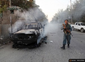 An Afghan policeman patrols next to a burning vehicle in the city of Kunduz, Afghanistan October 1, 2015. REUTERS/Stringer