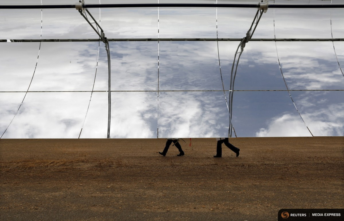 Staff walk behind solar collector assemblies at the Andasol solar power station near Guadix, southern Spain August 11, 2015. The plant is the biggest solar farm in the world and provides electricity for up to about 500,000 people. The 620,000 curved mirrors harness the sun's power even after dark, and the glass alone would cover 1.5 square km (0.6 square miles) - the size of about 210 soccer pitches. REUTERS/Marcelo del Pozo