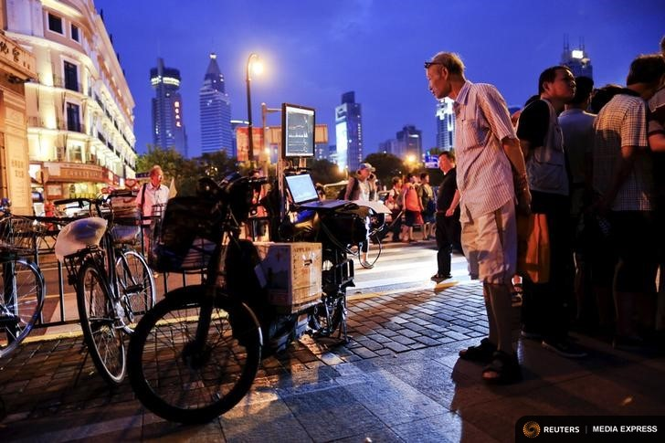 "Lv Hai looks at a screen displaying a stock analysis software, fixed to the back of an electric bicycle, during a ""street stock salon"" in central Shanghai, China, September 5, 2015. For at least a decade, an area next to the People's Square temporarily has transformed itself into a ""street stock salon"" during weekends, with investors from all over Shanghai coming to gather stock information and learn trading skills from others. A few businessmen also make use of the occasion to promote their stock analysis software. REUTERS/Aly Song"