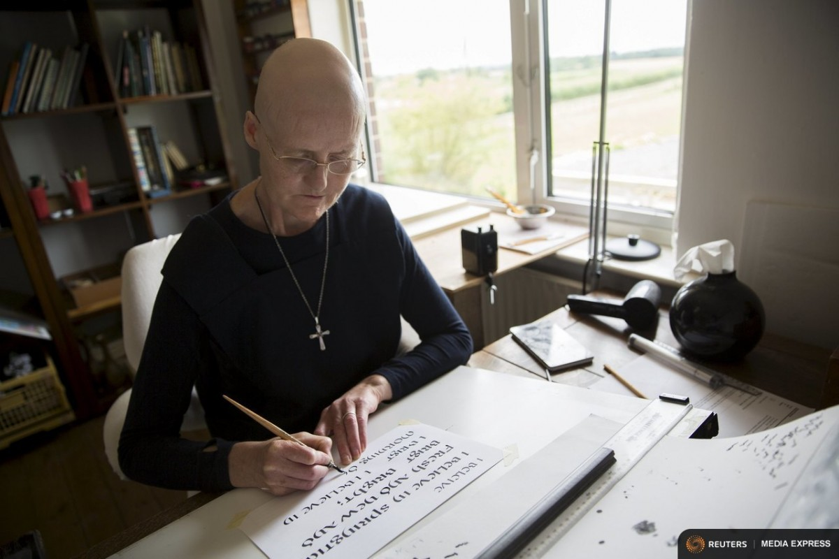 "Sister Rachel Denton practices her calligraphy St Cuthbert's Hermitage in Lincolnshire, north east Britain August 24, 2015. Denton, a Catholic hermit, rises early to tend to her vegetable garden, feed her cats and pray. But the former Carmelite nun, who in 2006 pledged to live the rest of her life in solitude, has another chore - to update her Twitter account and check Facebook. ""The myth you often face as a hermit is that you should have a beard and live in a cave. None of which is me,"" says the ex-teacher. For the modern-day hermit, she says social media is vital: ""tweets are rare, but precious,"" she writes on her Twitter profile. The internet also allows Denton to shop online and communicate with friends. ""I am a hermit but I am also human."" A diagnosis of cancer earlier this year reaffirmed Denton's wish to carry on a life of solitude, prayer and contemplation. REUTERS/Neil Hall"