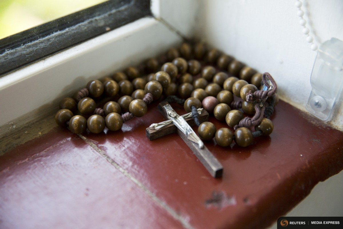 "A crucifix and rosary beads lie on a windowsill in St Cuthbert's Hermitage in Lincolnshire, north east Britain April 27, 2015. Denton, a Catholic hermit, rises early to tend to her vegetable garden, feed her cats and pray. But the former Carmelite nun, who in 2006 pledged to live the rest of her life in solitude, has another chore - to update her Twitter account and check Facebook. ""The myth you often face as a hermit is that you should have a beard and live in a cave. None of which is me,"" says the ex-teacher. For the modern-day hermit, she says social media is vital: ""tweets are rare, but precious,"" she writes on her Twitter profile. The internet also allows Denton to shop online and communicate with friends. ""I am a hermit but I am also human."" A diagnosis of cancer earlier this year reaffirmed Denton's wish to carry on a life of solitude, prayer and contemplation. REUTERS/Neil Hall"