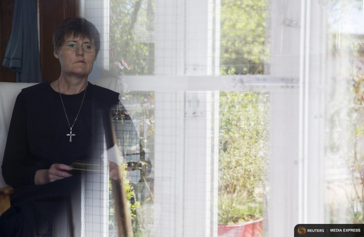 "Sister Rachel Denton looks out of a window at St Cuthbert's Hermitage in Lincolnshire, north east Britain April 27, 2015. Denton, a Catholic hermit, rises early to tend to her vegetable garden, feed her cats and pray. But the former Carmelite nun, who in 2006 pledged to live the rest of her life in solitude, has another chore - to update her Twitter account and check Facebook. ""The myth you often face as a hermit is that you should have a beard and live in a cave. None of which is me,"" says the ex-teacher. For the modern-day hermit, she says social media is vital: ""tweets are rare, but precious,"" she writes on her Twitter profile. The internet also allows Denton to shop online and communicate with friends. ""I am a hermit but I am also human."" A diagnosis of cancer earlier this year reaffirmed Denton's wish to carry on a life of solitude, prayer and contemplation. REUTERS/Neil Hall"