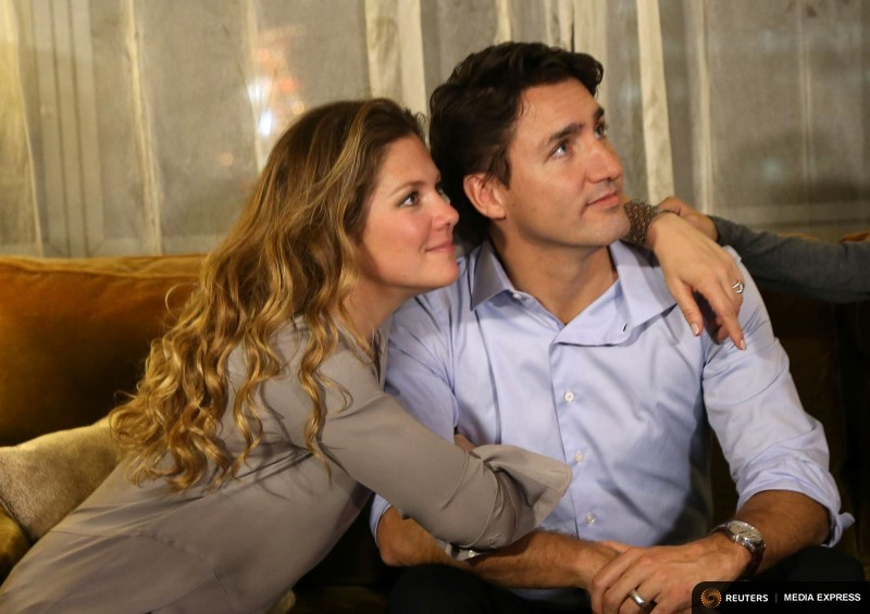 Justin Trudeau is embraced by his wife Sophie Gregoire as he watches results at his election night headquarters in Montreal, Quebec, October 19, 2015. REUTERS/Chris Wattie