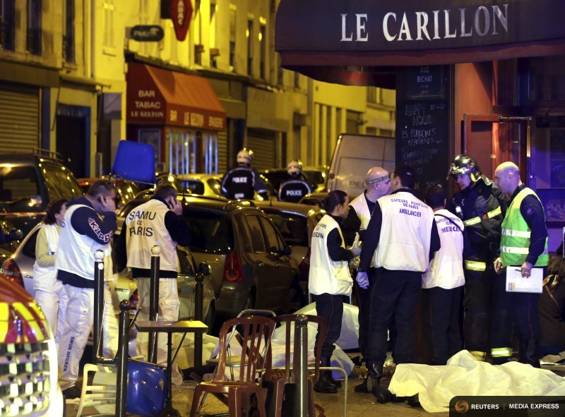 A general view of the scene shows rescue service personnel working near the covered bodies outside a restaurant following a shooting incident in Paris, France, November 13, 2015.   REUTERS/Philippe Wojazer