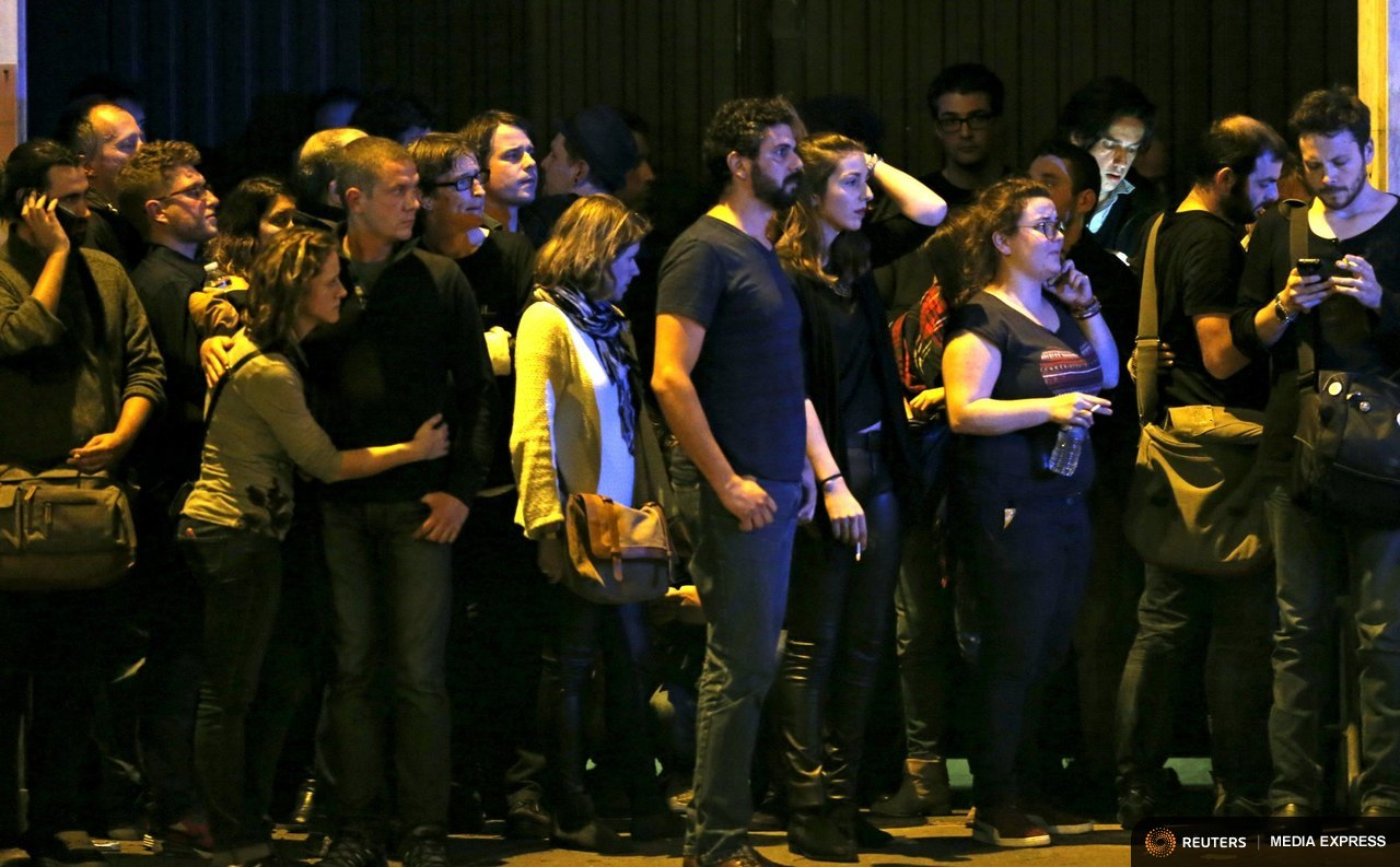 People react as they gather to watch the scene near the Bataclan concert hall following fatal shootings in Paris, France, November 13, 2015.  REUTERS/Christian Hartmann