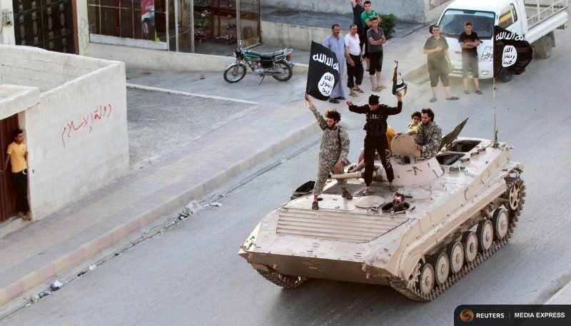 Militant Islamist fighters hold the flag of Islamic State (IS) while taking part in a military parade along the streets of northern Raqqa province in this June 30, 2014 file photo. REUTERS/Stringer