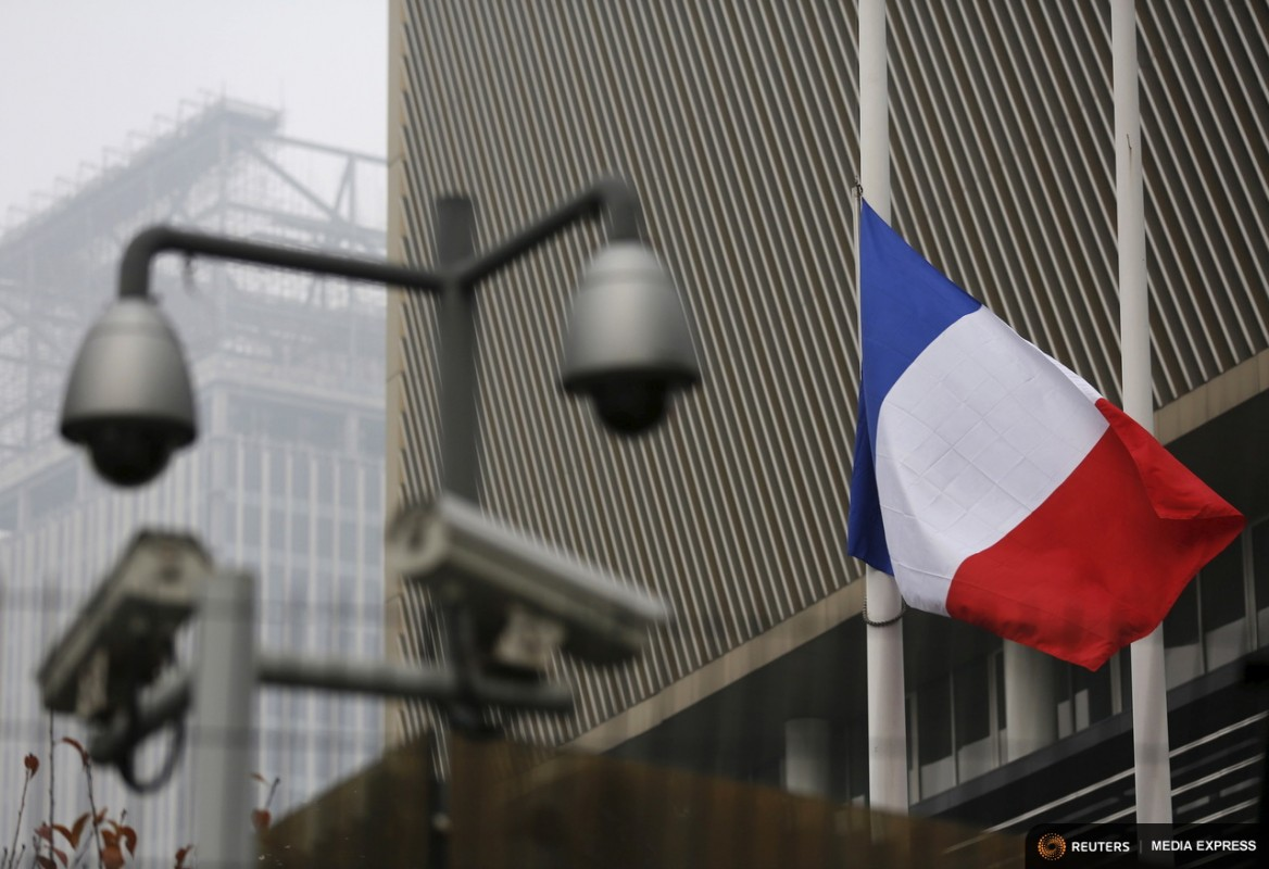 A French national flag flying at half-mast is seen behind security cameras at the French embassy in Beijing, China, November 14, 2015, after attacks in Paris on Friday. REUTERS/Kim Kyung-Hoon