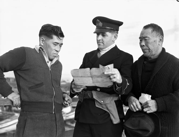 A Canadian naval officer confiscates a fishing boat from its Japanese Canadian owners during WWII. Photo: R.C.N. DND - Library and Archives Canada DAPDCAP 556450