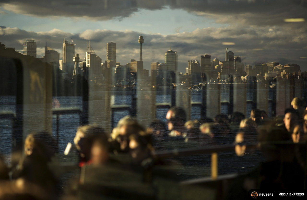 Commuters are bathed in mid-winter afternoon sunlight as Sydney's skyline is reflected in a window on their way home aboard the Manly ferry, July 2, 2015. Sydney's ferry system has been its lifeblood since the mid 1800s, transporting more than 15 million individual passenger journeys each year, according to the Bureau of Transport Statistics. From fast-food employees to finance industry executives, more than 40,000 trips are taken every day. Picture taken July 2, 2015. REUTERS/Jason Reed