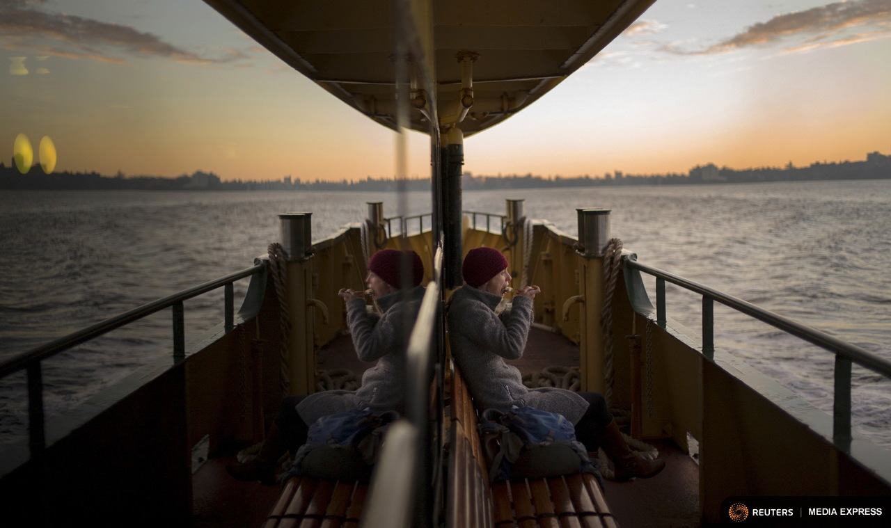 American-born Nina Leatherday eats her hot oats breakfast before sunrise as she braves 9 degree celsius (48 fahrenheit) mid-winter temperatures on the outside deck of a Sydney ferry from Manly to Circular Quay, June 30, 2015. Leatherday, a native of Michigan is an employee of Australia's Arnott's biscuit makers and prefers her daily ferry commute on the outside deck regardless of the weather. The ferry is but one leg of her daily journey to work, completed with a train ride into the suburbs of western Sydney. Sydney's ferry system has been its lifeblood since the mid 1800s, transporting more than 15 million individual passenger journeys each year, according to the Bureau of Transport Statistics. From fast-food employees to finance industry executives, more than 40,000 trips are taken every day. Picture taken June 30, 2015. REUTERS/Jason Reed