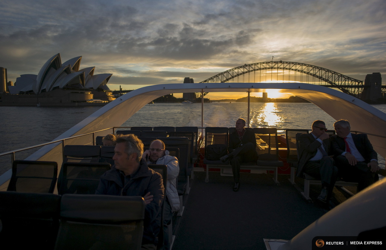 Commuters ride on the rooftop deck of a Sydney ferry at sunset en route to Rose Bay in Sydney's eastern suburbs, July 14, 2015. Sydney's ferry system has been its lifeblood since the mid 1800s, transporting more than 15 million individual passenger journeys each year, according to the Bureau of Transport Statistics. From fast-food employees to finance industry executives, more than 40,000 trips are taken every day. Picture taken July 14, 2015. REUTERS/Jason Reed