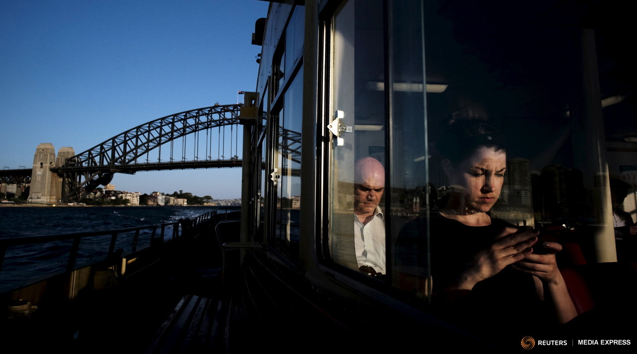 A commuter uses her mobile phone as a Circular Quay to Cockatoo Island ferry passes under the Sydney Harbour Bridge, November 24, 2015. Sydney's ferry system has been its lifeblood since the mid 1800s, transporting more than 15 million individual passenger journeys each year, according to the Bureau of Transport Statistics. From fast-food employees to finance industry executives, more than 40,000 trips are taken every day. Picture taken November 24, 2015. REUTERS/Jason Reed