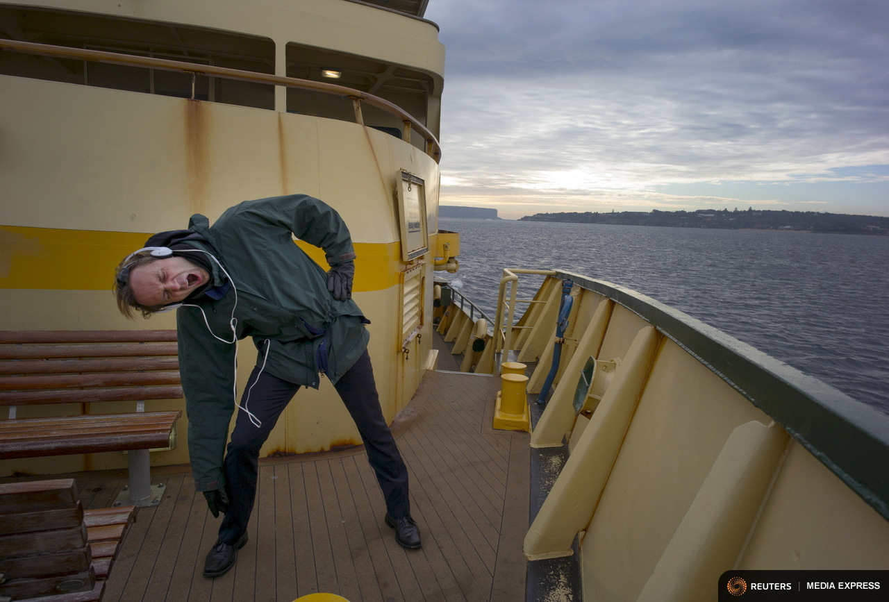 Corporate affairs executive Jake Krausmann yawns as as he performs his morning exercise routine on the bow of a Circular Quay-bound ferry from the northern beaches suburb Manly, June 30, 2015. The Manly ferry has been country-born Krausmann's preferred commute for 10 years, saying that he has always travelled on the outside decks in any weather and never gets sick of the trip. Sydney's ferry system has been its lifeblood since the mid 1800s, transporting more than 15 million individual passenger journeys each year, according to the Bureau of Transport Statistics. From fast-food employees to finance industry executives, more than 40,000 trips are taken every day. Picture taken June 30, 2015. REUTERS/Jason Reed