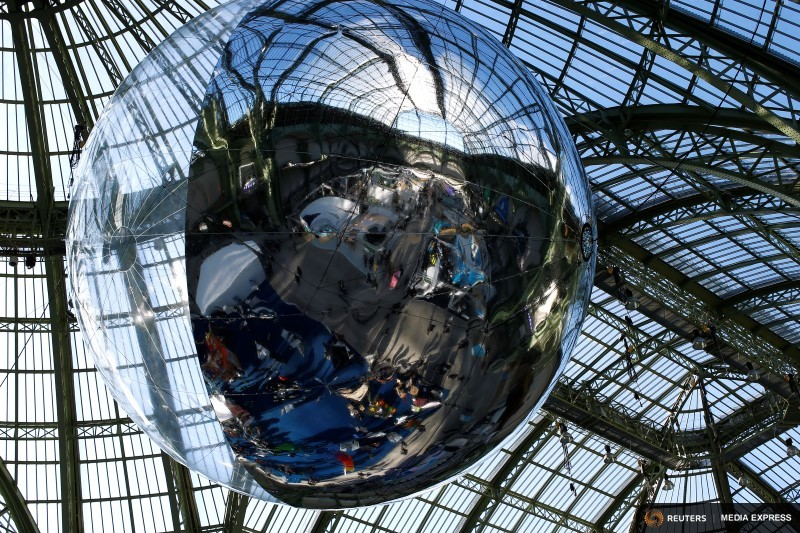Visitors and ecological stands are reflected on a giant ball suspended from the roof of the Grand Palais during the Solutions COP21 in Paris, France, December 4, 2015 as the World Climate Change Conference 2015 (COP21) continues at Le Bourget near the French capital. REUTERS/Benoit Tessier