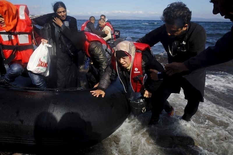 A Palestinian volunteer doctor helps Syrian refugees disembark a raft at a beach on the Greek island of Lesbos October 25, 2015. According to United Nations over half a million refugees and migrants have arrived by sea in Greece this year and the rate of arrivals is rising, in a rush to beat the onset of freezing winter. REUTERS/Yannis Behrakis - RTX1T4FC