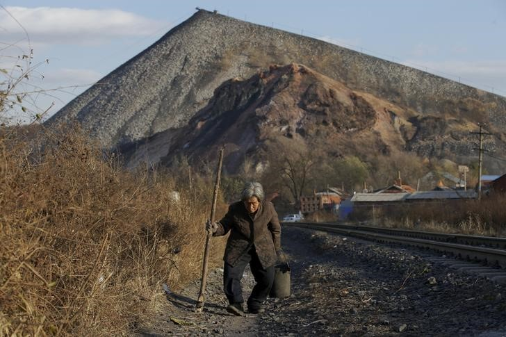 An elderly villager walks along a railway, which is used to transfer coal, in front of a coal gangue hill outside Shuanghe coal mine from the state-owned Longmay Group on the outskirts of Jixi, in Heilongjiang province, China, October 24, 2015. To match story CHINA-COAL/JIXI    Picture taken on October 24, 2015. REUTERS/Jason Lee