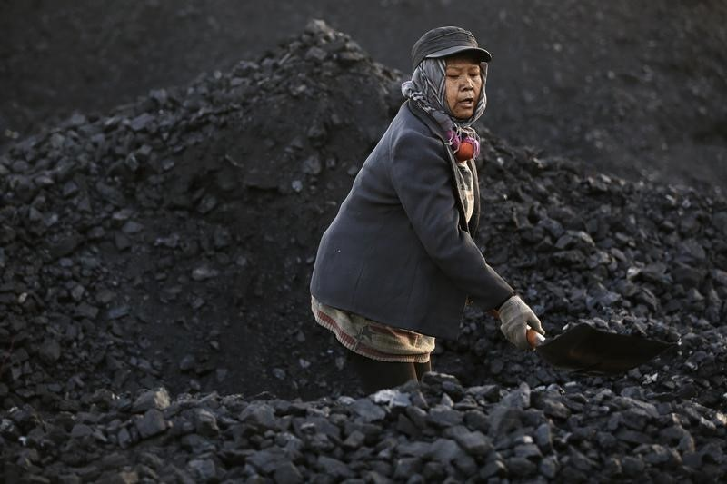A villager moves coal at local businessman Sun Meng's small coal depot near a coal mine of the state-owned Longmay Group on the outskirts of Jixi, in Heilongjiang province, China, October 23, 2015. To match story CHINA-COAL/JIXI Picture taken on October 23, 2015. REUTERS/Jason Lee