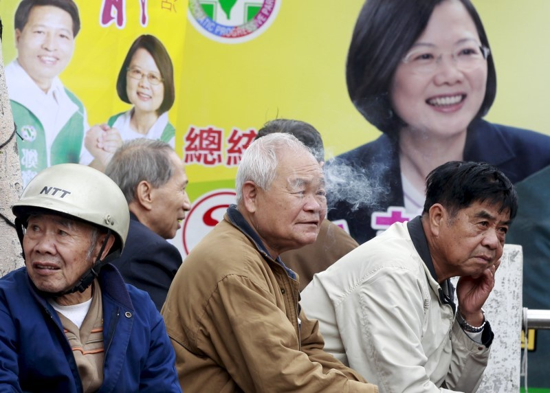 Supporters of Democratic Progressive Party (DPP) Chairperson and presidential candidate Tsai Ing-wen wait in front of her poster before a campaign rally starts for the 2016 presidential election in Taoyuan, northern Taiwan, January 7, 2016. REUTERS/Pichi Chuang