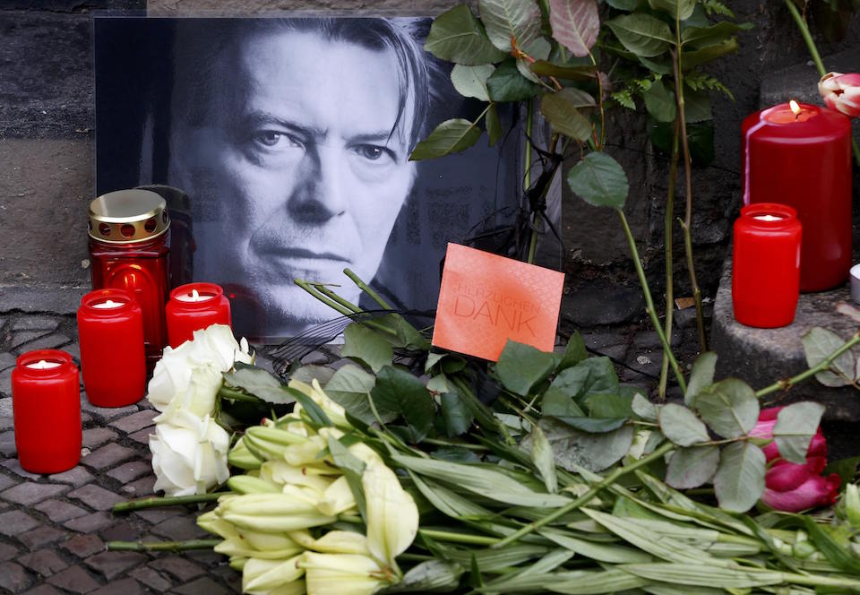 "Flowers and lit candles are pictured next to a portrait of David Bowie outside the apartment house where he was living in 1976-78 in Berlin's Schoeneberg district, Germany, January 11, 2016. David Bowie, a music legend who used daringly androgynous displays of sexuality and glittering costumes to frame legendary rock hits ""Ziggy Stardust"" and ""Space Oddity"", has died of cancer aged 69. REUTERS/Fabrizio Bensch"