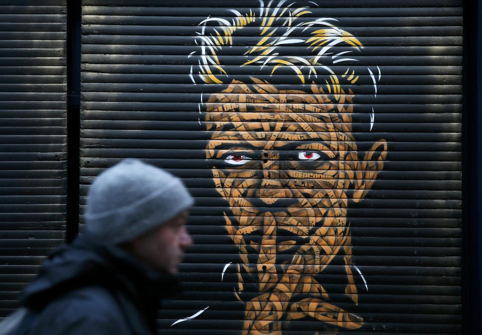A man walks past a painting of David Bowie of shop sutters in Brixton market, south London, January 11, 2016. REUTERS/Stefan Wermuth
