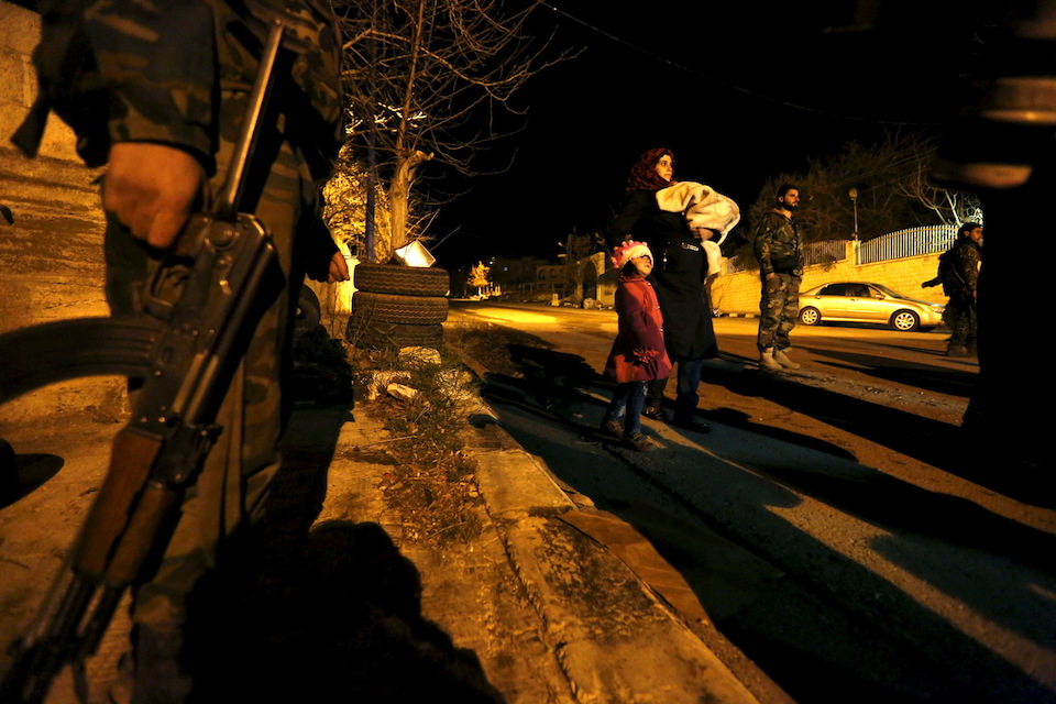 Residents, who say they have received permission from the Syrian government to leave the besieged town, walk past Syrian Army soldiers as they depart after an aid convoy entered Madaya, Syria, January 11, 2016. REUTERS/Omar Sanadiki