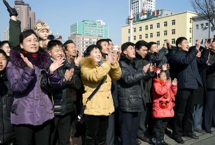 "North Koreans watching a huge screen broadcasting an official announcement that the country ""successfully"" put an Earth observation satellite into orbit, calling it an ""epoch-making"" achievement, applaud in Pyongyang, North Korea, in this photo released by Kyodo February 7, 2016. REUTERS/Kyodo"