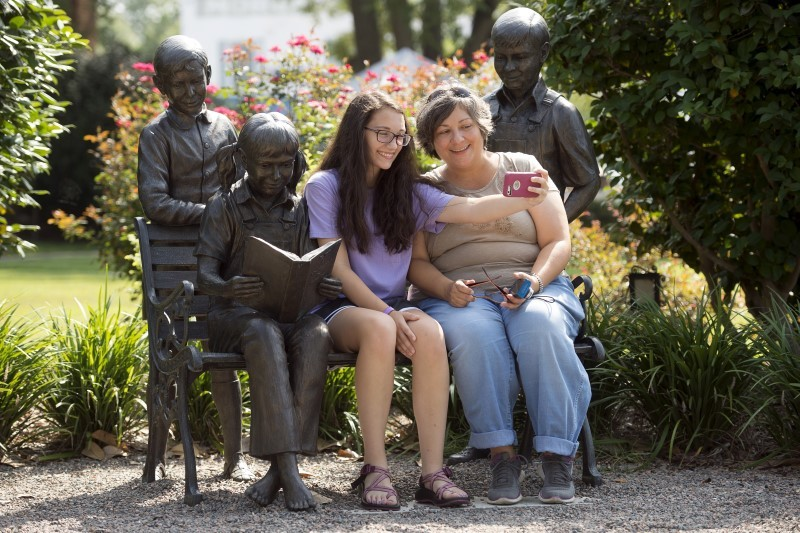 """Amy Burchfield and her daughter Scout Burchfield take a photo with the """"A Celebration of Reading"""" sculpture at the Old Monroe County Courthouse, the setting of """"To Kill a Mockingbird"""" in Monroeville, Alabama July 14, 2015. REUTERS/Michael Spooneybarger"""